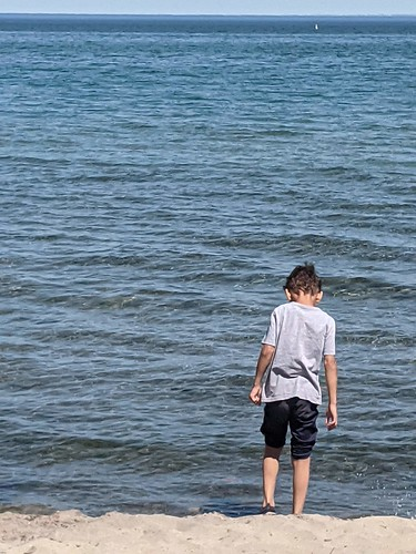 A boy is standing in brown sand at the shore of Lake Onario.  He is wearing sandals and has pushed his pants up to his knees.  He is putting his weight on his right leg and looking down.  The lake is in front of him with the horizon showing the clear blue sky.