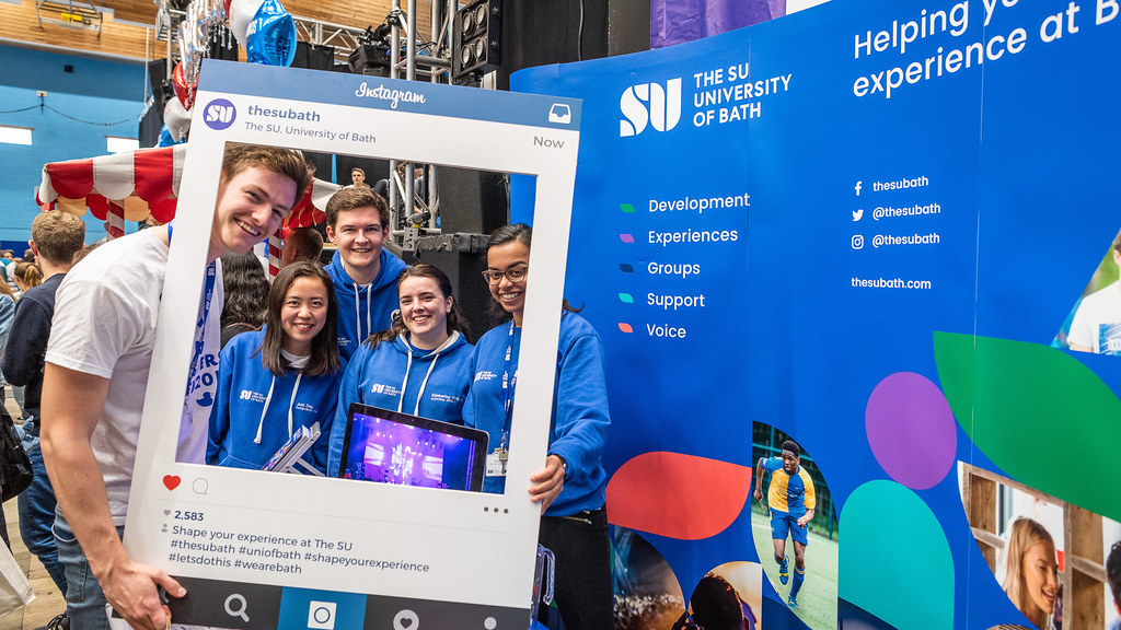 Students posing with a large frame at the Freshers' Fair.