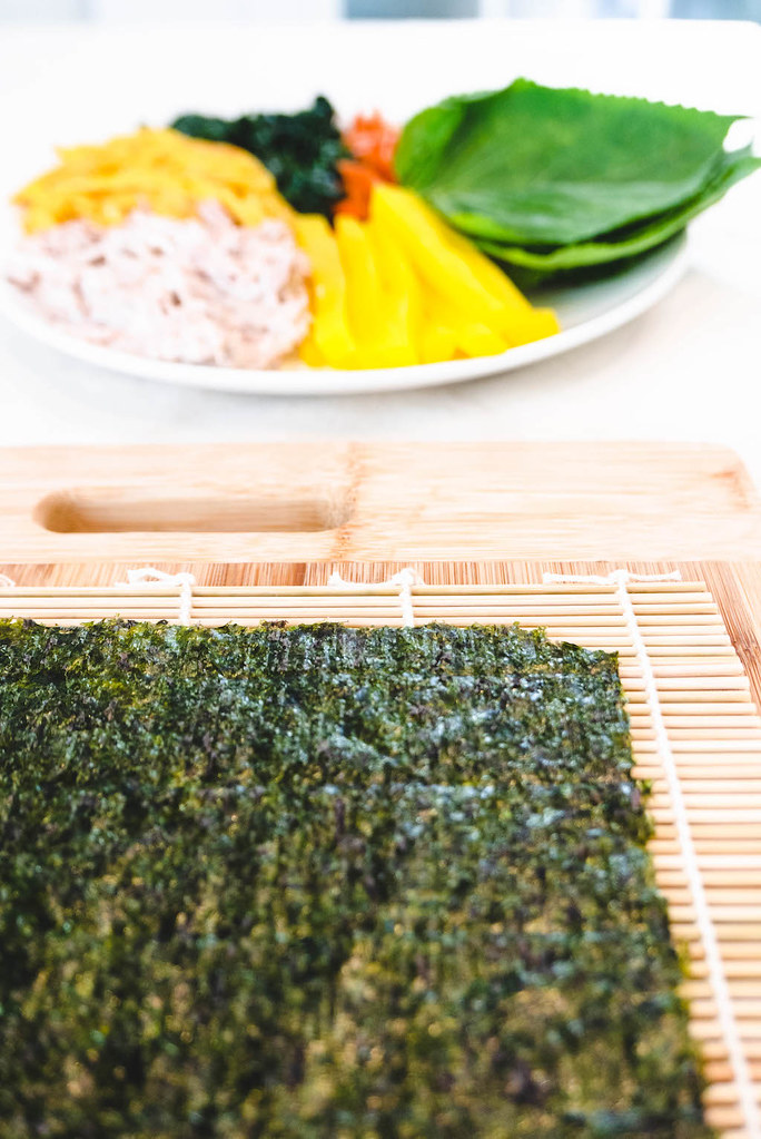 A close up shot of dried seaweed with the filler ingredients in the back.