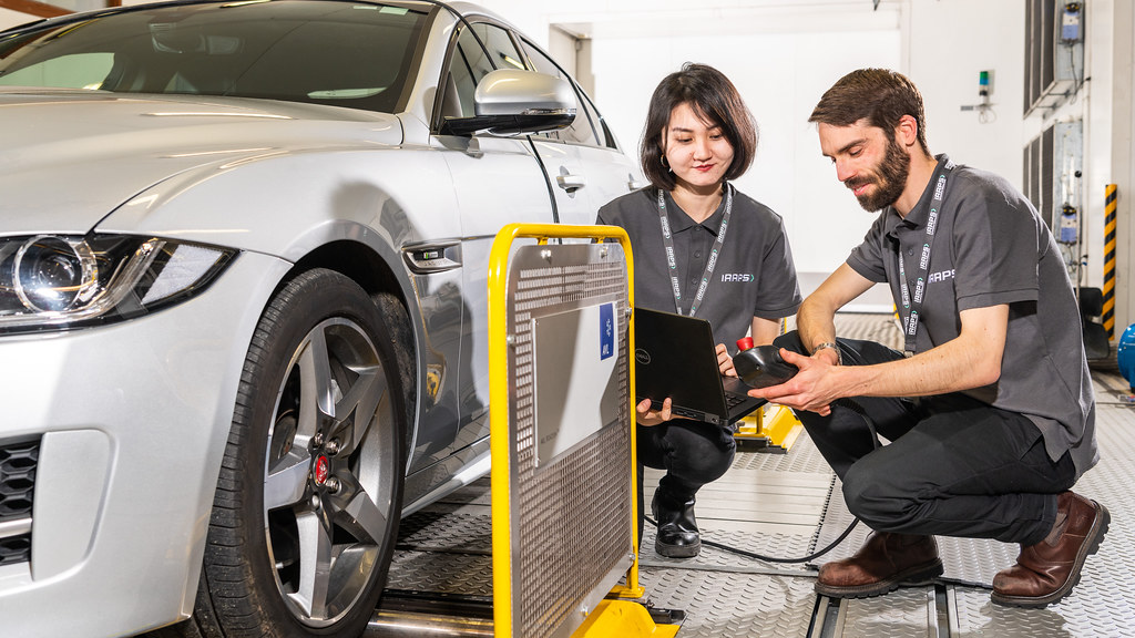 Two researchers inspecting a car.