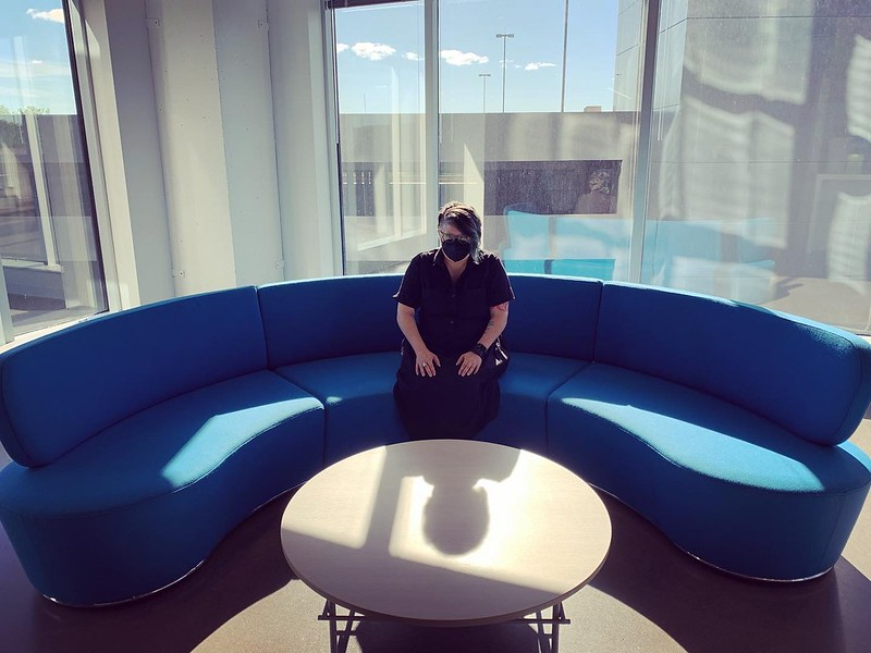 Me, sitting on a large, curved blue couch in my company's new office