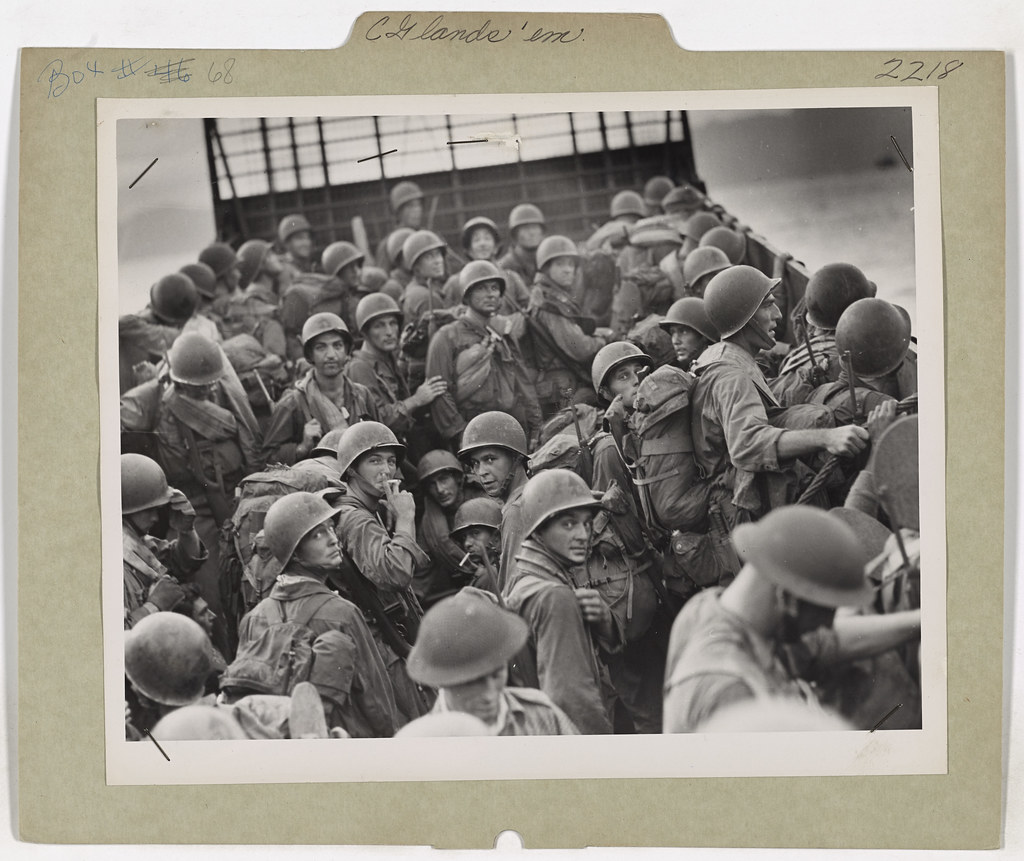 American troops, transferred from a Coast Guard-manned assault transport to a Coast Guard-manned landing craft, move in to attack the beach at Aitape in the Hollandia invasion.