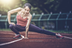 asia woman on running track stretching before run