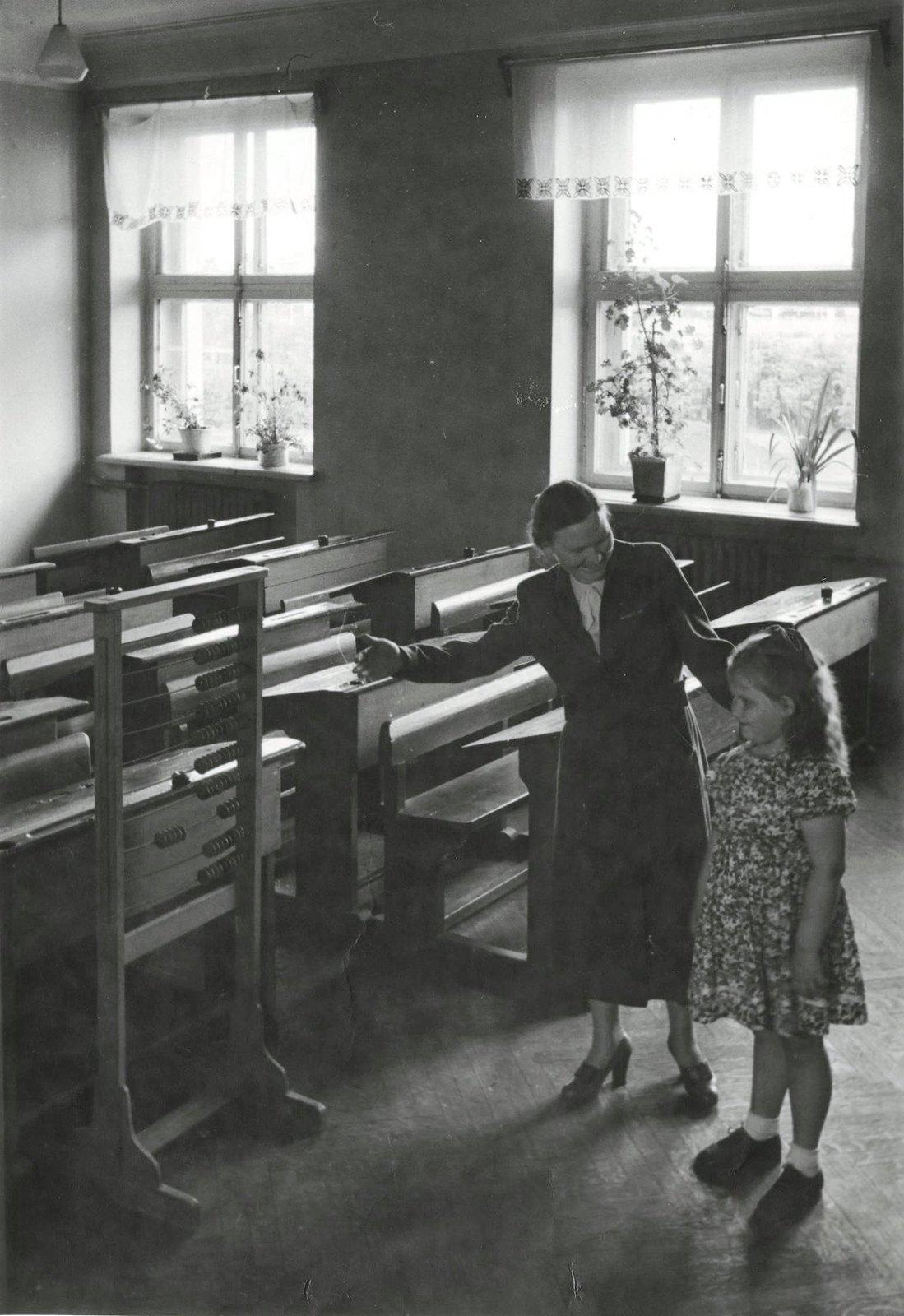 1950. Вот твой класс, твоя парта. Здесь ты будешь учиться, - говорит педагог будущей первокласснице