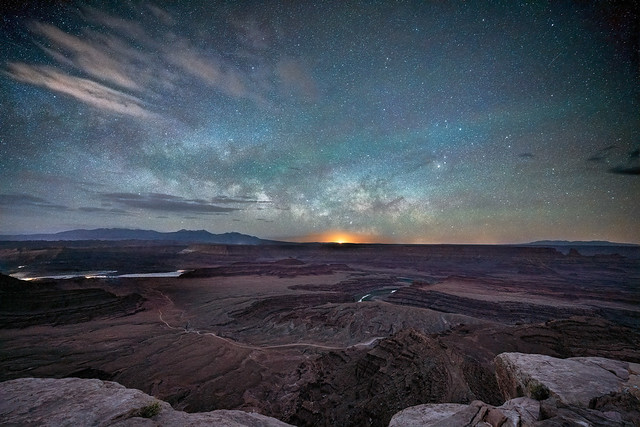 The Waning Gibbous moon rises just under the rising Milky Way core over Dead Horse Point with the silhouetted La Sal Mountains on the left.