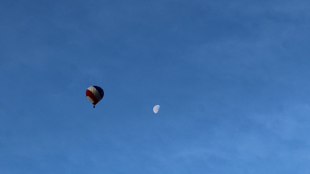 Hot air balloon in parallel with moon