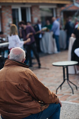 An obese man sitting at a party. Back view.