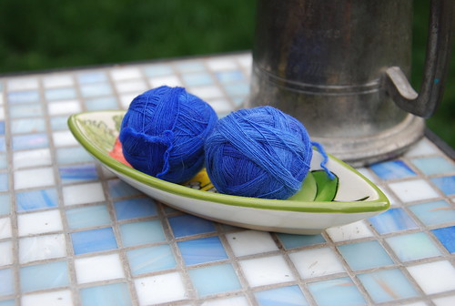 Two outer-pull balls of handspun Targhee wool singles by irieknit are dyed a saturated royal blue and rest in a small pea-pod shaped painted ceramic bowl that is white on the outside with green rim.  The bowl is laid diagonally on a mosaic tile table with blue and white square tiles and a pewter mug with handle is behind the bowl.