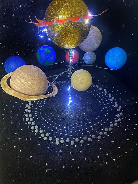 """014 - Sistema Solare di Fabiana 11 anni_a  Bella la superficie del sole che riflette con le bandierine arancioni a sottolineare il suo """"centro"""". Molto curato lo sfondo, gli elementi tridimensionali in circolo accompagnano e amplificano la potenza compositiva."""