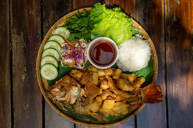 Top View Food Photo of Fried Tilapia Fish on a Bamboo Plate with Sliced Cucumber, Mixed Salad, Rice and Tamarind Sauce at a Vietnamese Restaurant