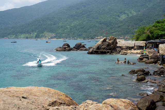 Jet Ski driving towards large Rocks at a Beach with Restaurant and Beach Bar with National Park in the Background on Son Tra Peninsula in Da Nang, Vietnam