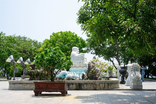Statues of White Laughing Buddha, Chinese Guardian Lions and a Dragon in front of Lady Buddha Statue at Linh Ung Pagoda in Da Nang, Vietnam