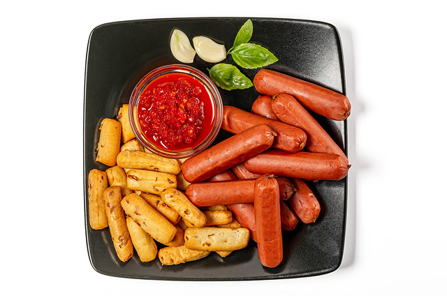 Onion crisps, smoked sausages and hot red sauce, top view