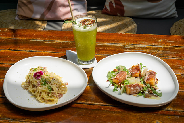 Food Photo of Healthy Fruit Juice in a Glas on a Wooden Table with Spaghetti Carbonara as Main Dish and Honeydew Melon wrapped in Parma Ham with Arugula and Parmesan Cheese as Appetizer