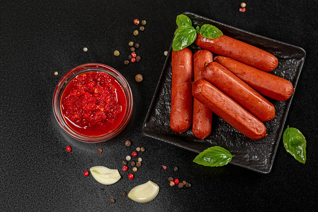 Smoked sausages and adjika with spices on a dark background