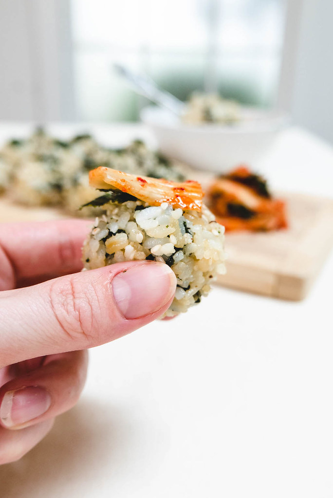 a photo of my hand holding a Korean rice ball with kimchi on top.