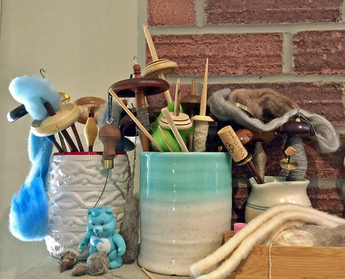 An arrangement of multiple drop and supported spindles in three containers on a concrete mantle with red brick fireplace surround.  The jar to the left is white with a cable knit relief pattern and red rim.  This jar is medium sized and 4 top-whorl spindles, 1 mid-whorl spindle is in the jar.  The middle jar is aqua fading to neutral glaze with a wide mouth.  One Kundert top-whorl spindle is to the right, 2 Peruvian low-whorl spindles and a supported spindle are in the jar.  The ring of a Golding drop spindle is behind grey fibre.  A smaller creamer is to the right with two coin takhlis that have corks protecting the tips, and three top-whorl spindles.  A bamboo box with cotton punis, a singles ball is in front of the creamer.  A blue Care Bear is in front of the white jar and small assorted objects are also on the mantle including a hand-wound outer-pull ball of grey wool.