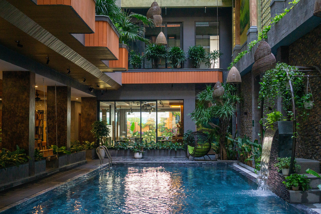 Artificial Waterfall with many Plants next to a Swimming Pool inside a Hotel with a lot of Daylight and modern Architecture