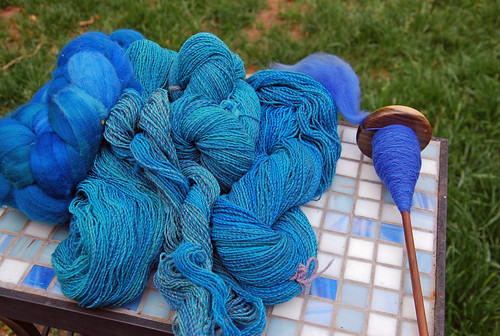 Left to right laid on a blue and white mosaic square tile side table in front of a green lawn is:  a braid of handpainted Targhee wool in blue and teal shades; 4 twisted skeins of fine three-ply handspun Targhee yarn in shades of a lighter blue; a top-whorl Bosworth drop-spindle with a cop of royal blue Targhee wool hanspun yarn and the working fibre to the top left of the whorl