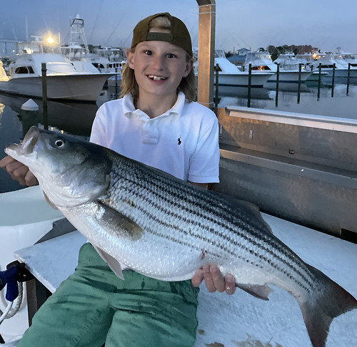 Photo of boy sitting on a dock with large striped bass
