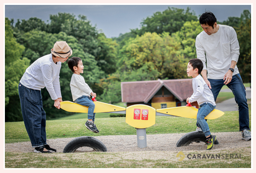 公園でシーソーをして遊ぶ家族