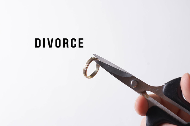 Divorce concept - person hand cutting wedding ring with scissors