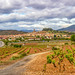 Beautiful May landscape with vineyards, red clay and the town of Navarrete in La Rioja, Spain in the distance