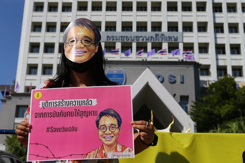 นักกิจกรรมแอมเนสตี้ อินเตอร์เนชั่นแนล ประเทศไทย สวมเสื้อฮาวายและหน้ากากวันเฉลิม