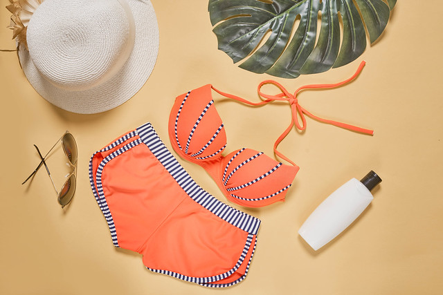 Cute female's bikini, sunglasses, straw hat and sunscreen cream on colored background