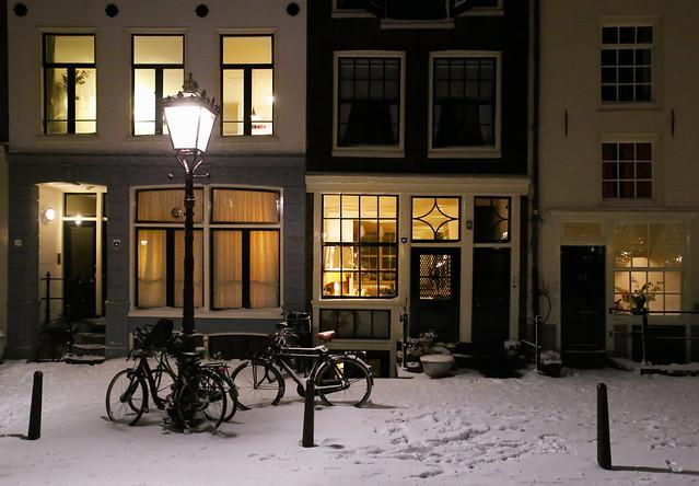 Amsterdam in winter wonderland with the warm idyllic home lights