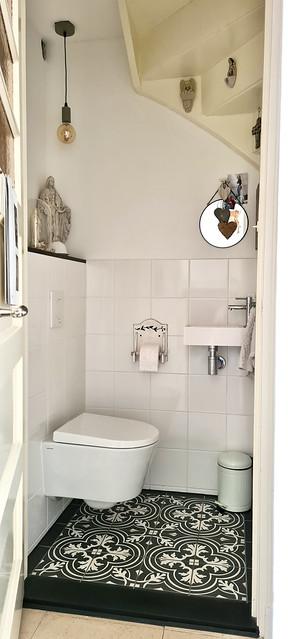 Toilet onder de trap zwartwit vloer religieuze beelden