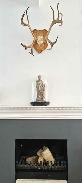 Grijze haard gewei schouw religieus beeld onder glazen stolp