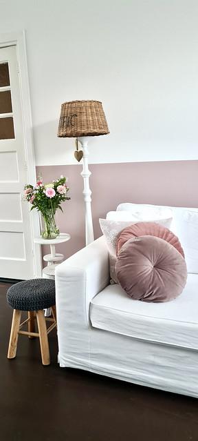 Witte bank met roze kussens roze muur rotan lampenkap gebreide kruk