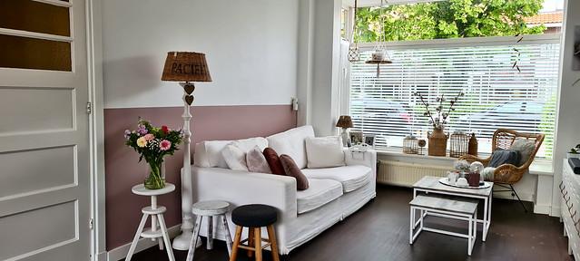 Roze muur lambrisering witte bank vlinderstoel met kussens gebreide kruk rotan windlicht