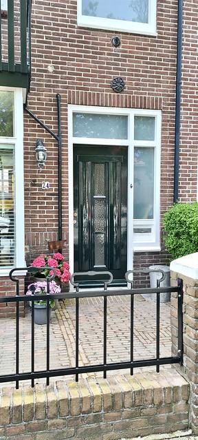 Groene hoogglans voordeur ijzeren hek voortuin