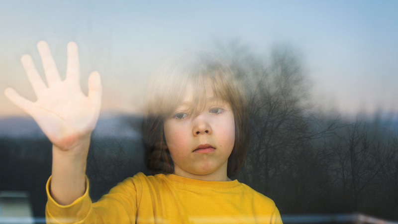 Young boy looking upset behind window with hand raised to the glass.