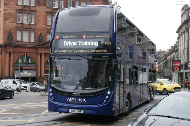 Lothian Volvo B8L Alexander Dennis Enviro XLB SB19GNF 1138, in the revised Airlink livery, on driver training duty turning from Lothian Road to Princes Street on 2 June 2021.