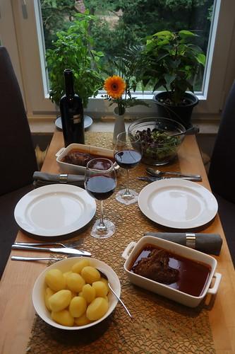 Lammhaxen in Tomatensoße mit Salzkartoffeln und Pflücksalat (Tischbild)