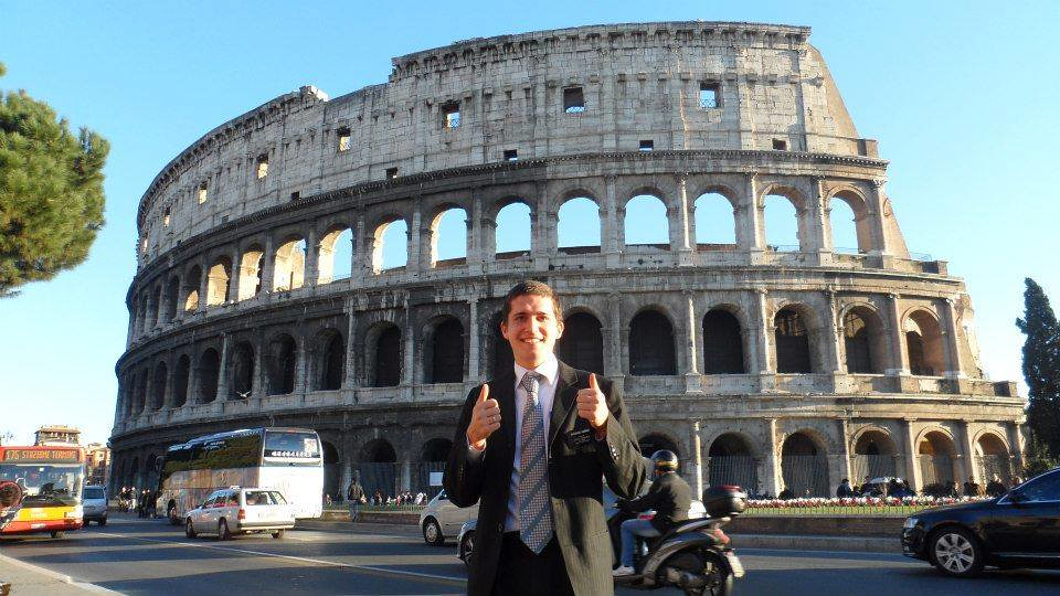An image of me in a black suit and missionary nametage giving thumbs-up in front of the colosseum
