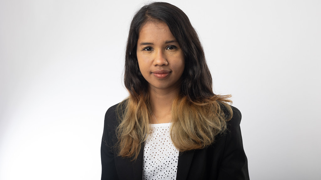 MSc International Student Kamakshi wears a white blouse and black blazer standing in front of a plain white background smiling at the camera.