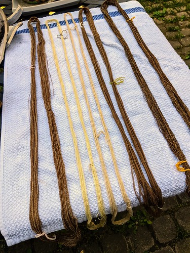Five skeins of wet handspun cotton by irieknit lie on a white cotton towel on a patio table outside for drying.