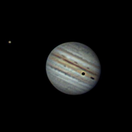 VCSE - Más képkivágásban látszik a Jupiter nagy koronjától balra, kissé felfelé egy sárgás színű jupiterhold: a ganymedes. Ennek árnyéka vetül fekete pöttkyént a gázbolygóra. - Kép: Fridrich János