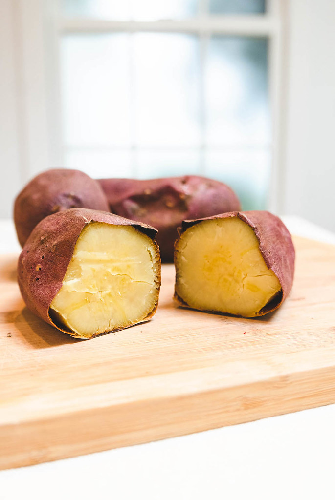 Cooked sweet potatoes on a cutting board.