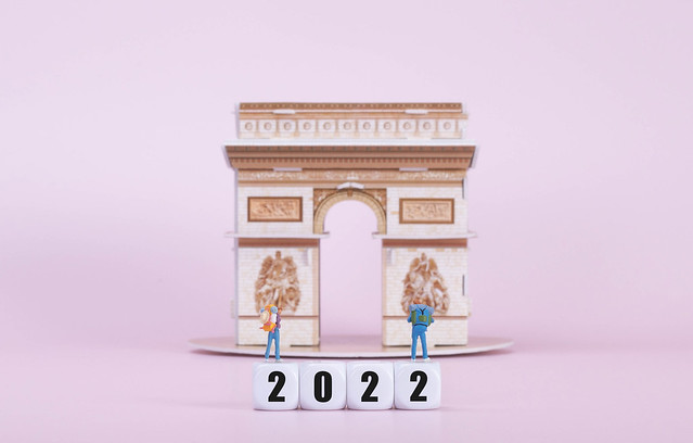 Two travelers standing on blocks with 2022 text in front of Arc de Triomphe