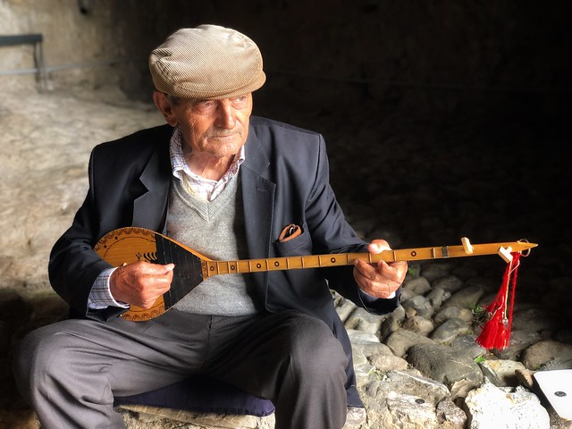 Músico callejero de Albania tocando su laúd a las puertas del castillo de Kruje
