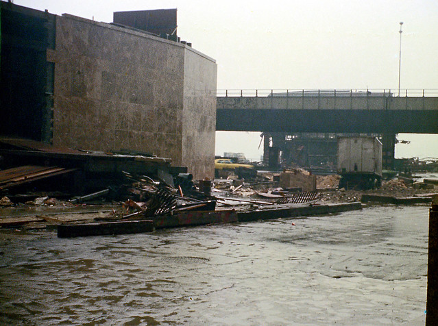 Welcome to 1970s Manhattan. The corner of Vesey and West Streets. Unfinished 6 World Trade Center on the left. Across West St, rusting 19th century piers line the Hudson. The abandoned West Side Highway slices through the scene. March 1973