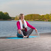 Mature Caucasian Blond Woman During Yoga Practice With Eyes Closed on Blue Mat At Water Shore Outdoor