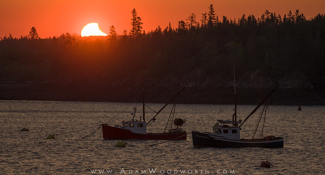 Partial Eclipse at Sunrise Over Fishing Boats