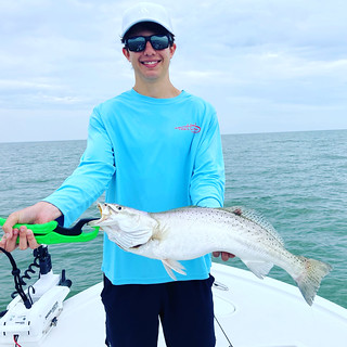 Photo of young man in boat holding a speckled trout