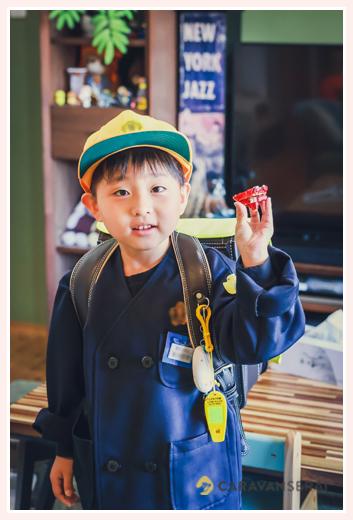 小学校の制服と帽子をみにつけランドセルを背負って記念写真